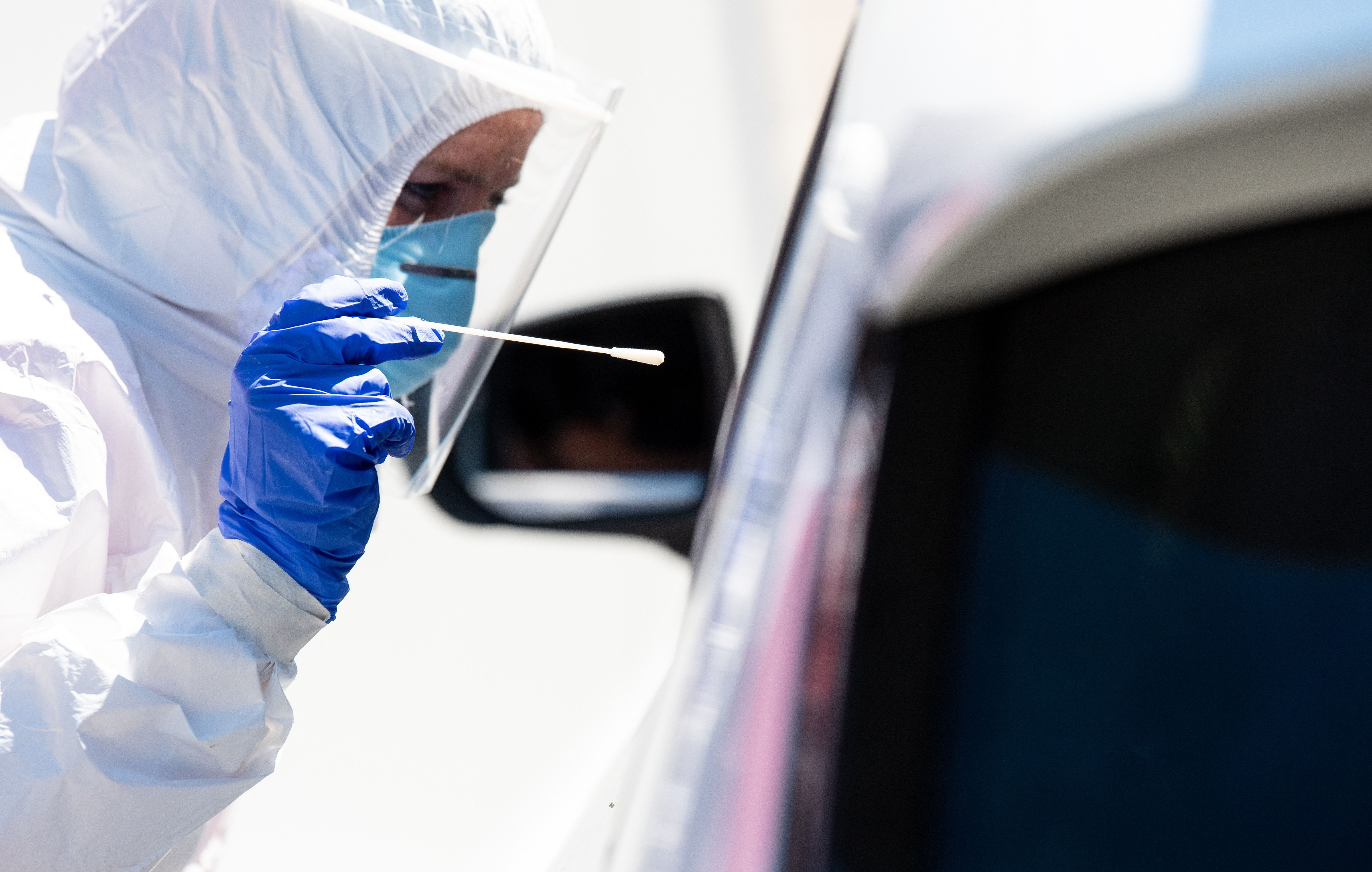 30 July 2020, Bavaria, Bergen: A health worker dressed in Personal Protective Equipment (PPE) takes a smear test from a car driver at a coronavirus (COVID-19) test centre on the motorway 8 (A8) at the Hochfelln-Nord rest area. Photo: Sven Hoppe/dpa